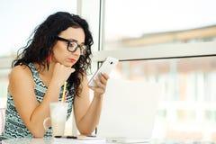 Belle jeune femme à l'aide de l'ordinateur portable et parlant au téléphone portable Photos libres de droits