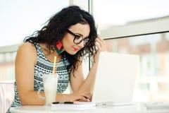 Belle jeune femme à l'aide de l'ordinateur portable et parlant au téléphone portable Photo libre de droits