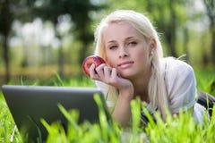 Belle jeune femme à l'aide de l'ordinateur portatif dans le stationnement Image libre de droits