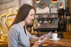 Belle jeune femme à l'aide de son PC de comprimé dans le coffe photos stock