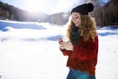 Belle jeune femme à l'aide de son téléphone portable au-dessus de backgro d'hiver Photo libre de droits