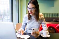 Belle jeune femme à l'aide du téléphone portable tout en travaillant avec son ordinateur portable dans le café Image libre de droits