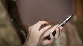 Belle jeune femme à l'aide du téléphone se reposant sur le divan à la maison Web surfant de femme, réseaux sociaux, regardant que clips vidéos
