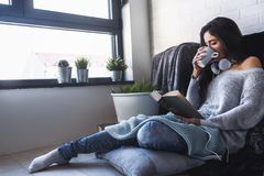 Belle jeune femme à la maison buvant du café lisant un livre Photos stock