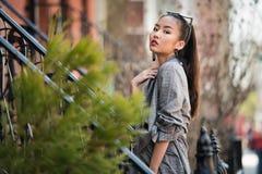 Belle jeune femme à la mode asiatique posant sur la rue de ville dehors photos libres de droits