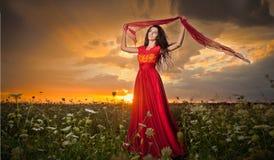 Belle jeune femme à la mode dans la longue pose rouge de robe extérieure avec le ciel dramatique nuageux à l'arrière-plan Brunett Images libres de droits