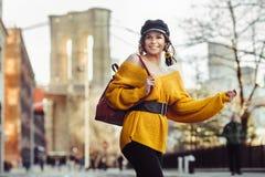 Belle jeune femme à la mode heureuse voyageant à New York City avec le sac à dos image stock
