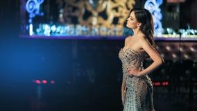 Belle jeune femme à la mode sexy dans la robe de soirée brillante d'or posant sur le fond de lampes au néon de nuit clips vidéos