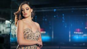 Belle jeune femme à la mode sexy dans la robe de soirée brillante d'or posant sur le fond de lampes au néon de nuit banque de vidéos