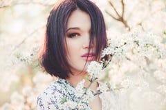 Belle jeune femme à Sakura de floraison Photographie stock libre de droits
