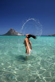 Belle jeune femme éclaboussant l'eau de ses cheveux. Photo libre de droits
