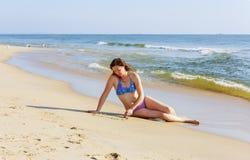 Belle jeune femme écrivant le mot AMOUR sur le sable Photographie stock