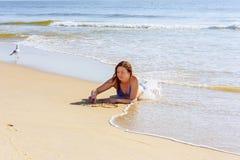 Belle jeune femme écrivant le mot AMOUR sur le sable Photos stock
