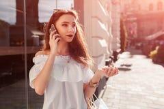Belle jeune femme élégante avec des paniers refroidissant sur la rue de ville et parlant au téléphone Image stock