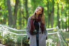 Belle jeune femme élégante dans un manteau confortable à la mode de blues-jean chaudes d'écharpe marchant le long en parc de vill Images stock
