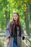 Belle jeune femme élégante dans un manteau confortable à la mode de blues-jean chaudes d'écharpe marchant le long en parc de vill Photographie stock libre de droits