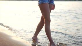 Belle jeune femme élégante heureuse à la mode parlant au téléphone, marchant sur le sable le long de la plage Jolie fille banque de vidéos