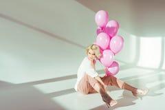 belle jeune femme élégante tenant les ballons roses et se reposer images stock