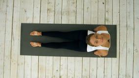 Belle jeune femme établissant à l'intérieur, faisant l'exercice de yoga dans la chambre, pose orientée vers le bas de chien, mukh clips vidéos