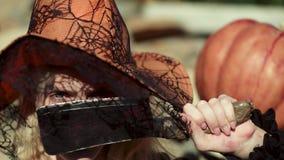 Belle jeune femme étonnée dans le chapeau de sorcière et le costume de Halloween Halloween drôle font face Décoration de vacances banque de vidéos