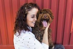 Belle jeune femme étreignant son chien, un chien d'eau espagnol brun Photographie stock libre de droits
