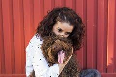 Belle jeune femme étreignant son chien, un chien d'eau espagnol brun Photo stock