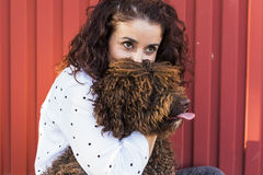 Belle jeune femme étreignant son chien, un chien d'eau espagnol brun Photos stock