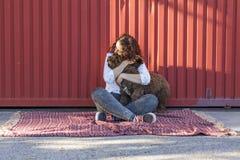Belle jeune femme étreignant son chien, un chien d'eau espagnol brun Image libre de droits