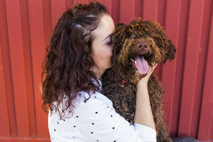 Belle jeune femme étreignant son chien, un chien d'eau espagnol brun Images libres de droits