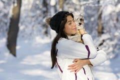 Belle jeune femme étreignant son petit chien blanc dans la forêt d'hiver Photographie stock libre de droits