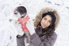 Belle jeune femme étreignant son petit chien blanc dans la forêt d'hiver temps de chute de neige Photos libres de droits