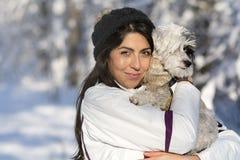 Belle jeune femme étreignant son petit chien blanc dans la forêt d'hiver temps de chute de neige Image libre de droits