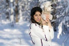 Belle jeune femme étreignant son petit chien blanc dans la forêt d'hiver temps de chute de neige Images libres de droits