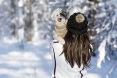 Belle jeune femme étreignant son petit chien blanc dans la forêt d'hiver temps de chute de neige Images stock