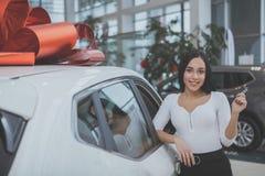 Belle jeune femme achetant la nouvelle voiture au concessionnaire image stock
