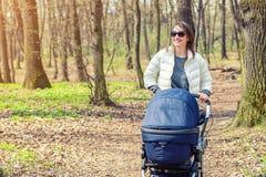 Belle jeune femme adulte marchant avec le bébé dans la poussette par la forêt ou le parc le jour ensoleillé lumineux Style de vie images libres de droits