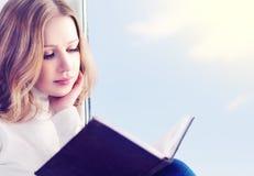 Belle jeune femme affichant un livre tout en se reposant à un hublot Images libres de droits