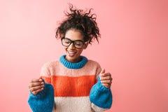 Belle jeune femme africaine émotive posant au-dessus du fond rose de mur tenant quelque chose apparence photos libres de droits