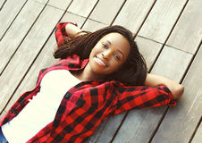 Belle jeune femme africaine de sourire décontractée sur le plancher en bois avec des mains derrière la tête, utilisant une chemis Photos libres de droits