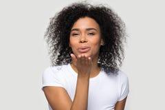 Belle jeune femme africaine envoyant le tir de studio de baiser d'air photographie stock