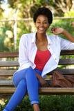 Belle jeune femme africaine s'asseyant sur un banc de parc Photo stock