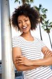 Belle jeune femme africaine se penchant à un poteau dehors et à rire images stock