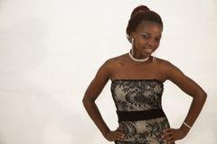 Belle jeune femme africaine tenant un verre de vin rouge Images stock