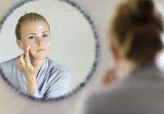 Belle jeune femme appliquant la crème de visage Photographie stock libre de droits