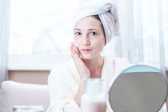 Belle jeune femme appliquant la crème des cosmétiques naturels sur le visage hydratant la peau Hygiène et entretenir la peau photo stock