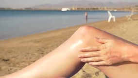 Belle jeune femme appliquant la protection solaire aux jambes à la plage HD banque de vidéos