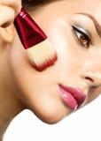 Jeune femme appliquant le maquillage image stock