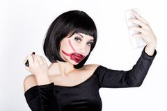 Belle jeune femme appliquant le rouge à lèvres rouge foncé, lèvres teintes laides Sur un fond blanc images stock