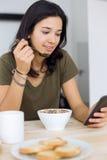 Belle jeune femme appréciant le petit déjeuner à la maison Photographie stock libre de droits