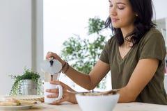 Belle jeune femme appréciant le petit déjeuner à la maison Image stock